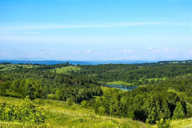 青い湖と夏の美しい丘の風景