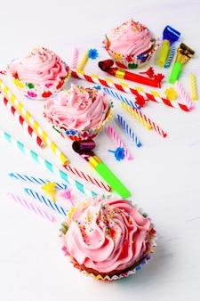 ピンクのホイップクリームの渦巻き、垂直の誕生日カップケーキ