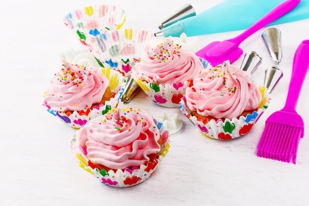 ピンクのホイップクリームの渦巻きと菓子注射器のカップケーキ