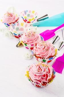 ホイップクリームと調理器具とピンクの誕生日カップケーキ