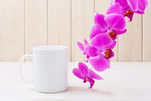 ピンクの蘭と白いコーヒーマグカップ