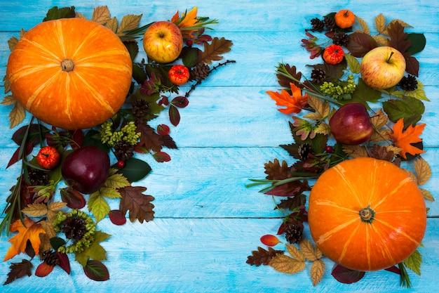 葉と青い木製のテーブルにカボチャの感謝祭の挨拶