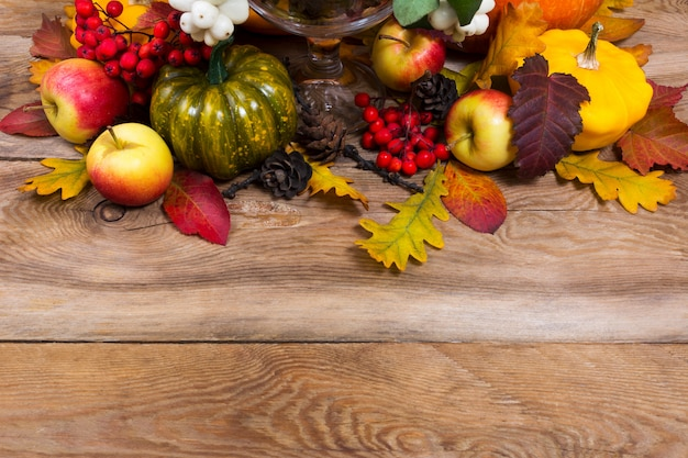 秋の背景に緑のカボチャ、黄色のカボチャ、カシの葉、コピースペース