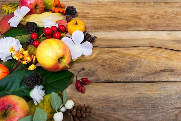 秋の背景に白い花、緑、黄色の葉、コピースペース