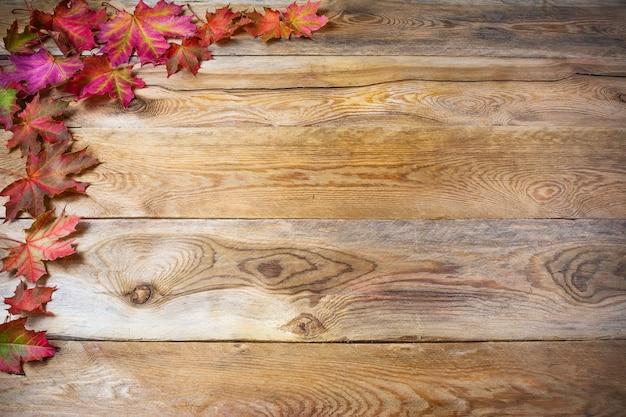 素朴な木製の背景に秋のカエデの葉と感謝祭の挨拶