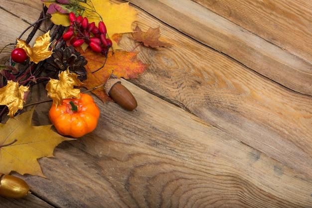 感謝祭の背景にカボチャ、金色のカエデの葉の花輪、
