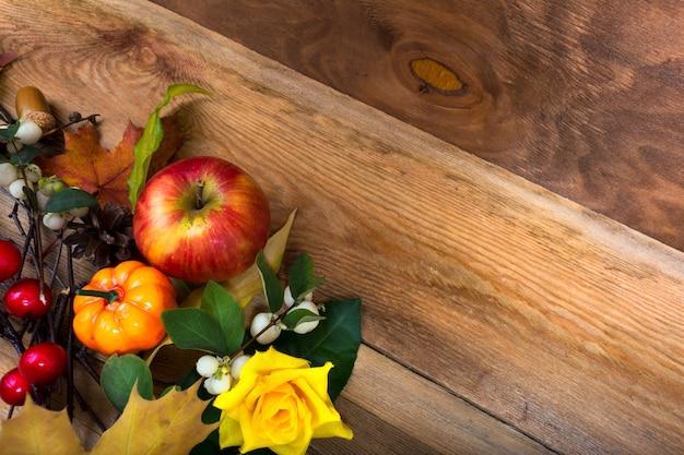 Деревенском фоне падения с яблоком, тыквой, желтой розой,
