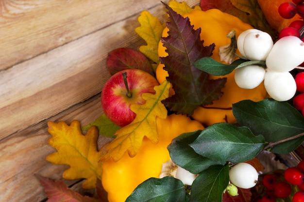 Осенний фон со снежноягодником и желтой тыквой