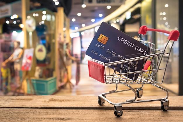 内側と後ろにクレジットカードを入れた小さなショッピングカートがぼやけています。ショップ - ショッピングの概念使用クレジット。