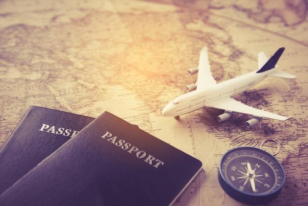 地図に載っているパスポート、飛行機、コンパス-コンセプトトラベル