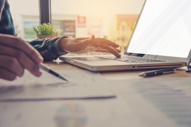 Деловые люди работают над учетными записями в бизнес-анализе с графиками и документацией.
