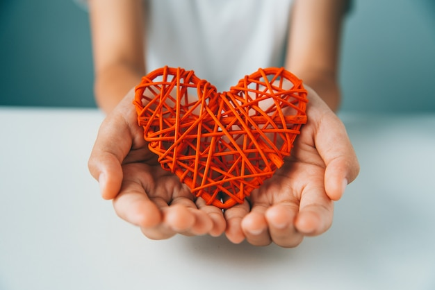 手は愛のために赤いハートを与える