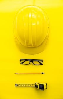 Желтый инженер по безопасности и картридж, карандаш, очки положить на желтую землю