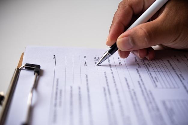 ペンでデスクで紙を書くとオフィスで働くテーブルで本を読む手のクローズアップ