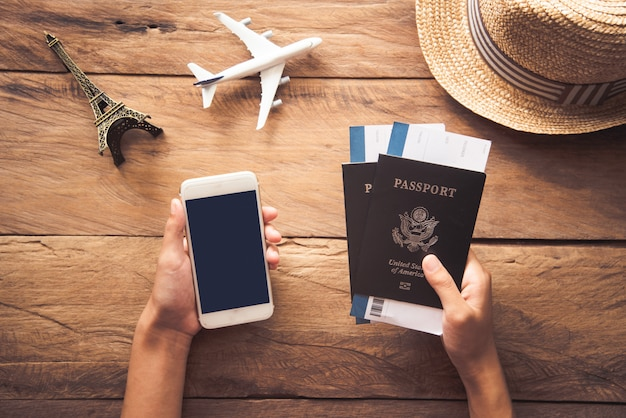 旅行者はパスポートとスマートフォンを保持しています。旅行とともに