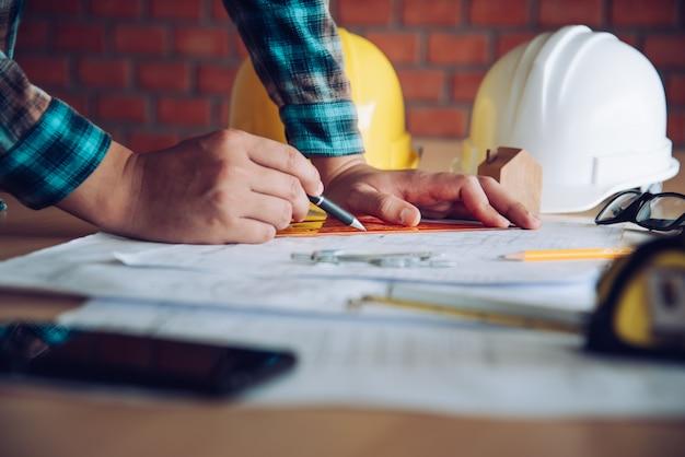 Инженер, работающий в офисе с чертежами, осмотр на рабочем месте для архитектурного плана, строительного проекта, бизнес концепции строительства.
