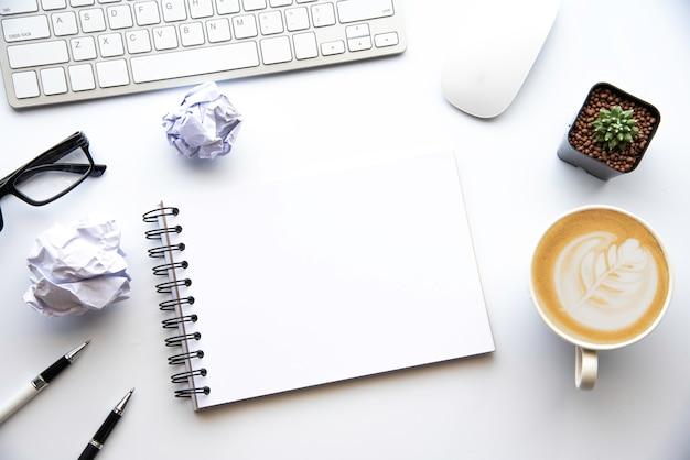 Вид сверху с копией пространства, рабочий стол с ноутбуком, мобильный телефон, карандаш для ноутбука и кофе на белом фоне