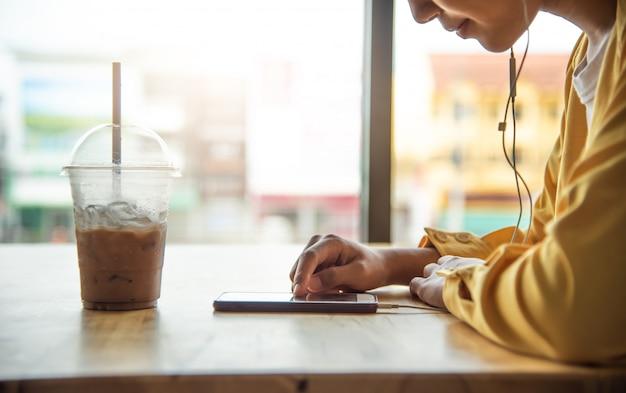Девушка наслаждается телефоном в кафе и выпивает бокал холодного напитка на переднем плане