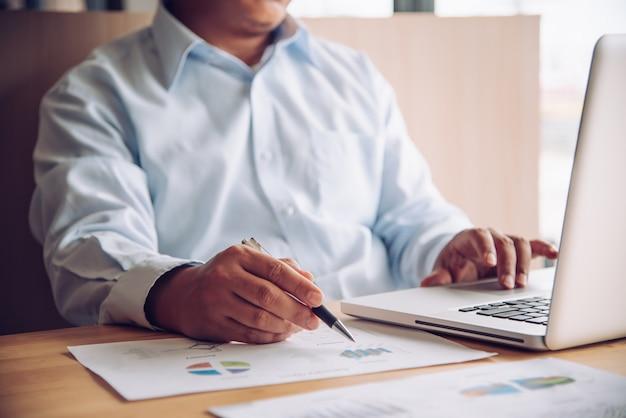 Бизнесмен работает с ноутбуком в офисе открытого пространства