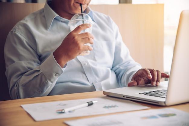 Молодой человек пьет кофе во время работы на ноутбуке