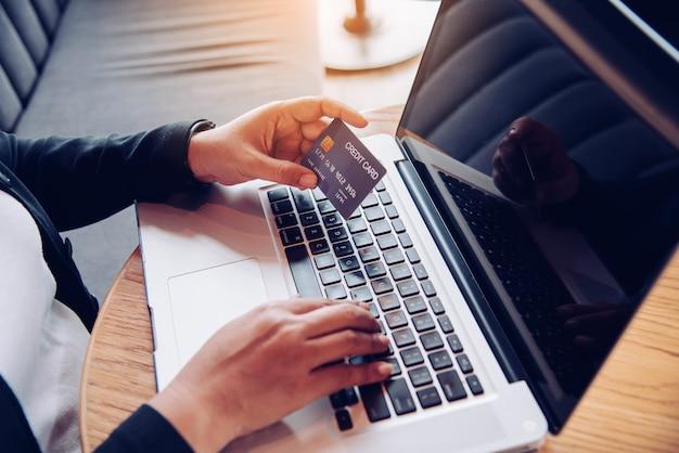 クレジットカードを手に持って、ラップトップデバイスを使用してオンラインで購入し、金融取引を行う製品に関する情報を見つける手。