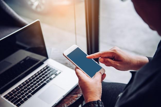 Бизнесмены используют смартфоны и ноутбук для подключения и поиска информации в офисе