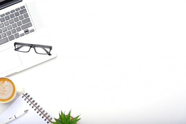 ノートパソコン、携帯電話、ノートブックの鉛筆のコーヒーカップ、オフィスで眼鏡の作業机の上から見る。