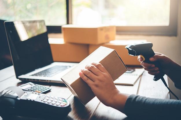Доставка сотрудников сканирует картонную коробку со сканером штрих-кода, чтобы проверить продукты для клиентов
