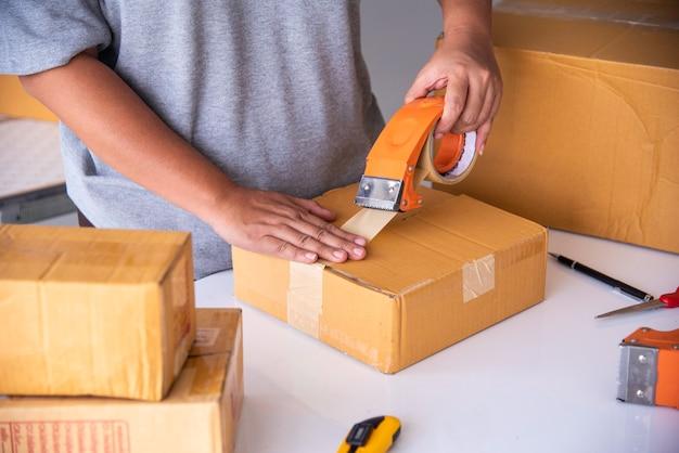 スタッフはテープを使用して、お客様にパッケージ商品を梱包しています。