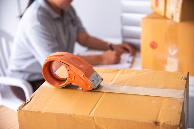 Персонал использует ленту, чтобы упаковать упаковку товара покупателю.