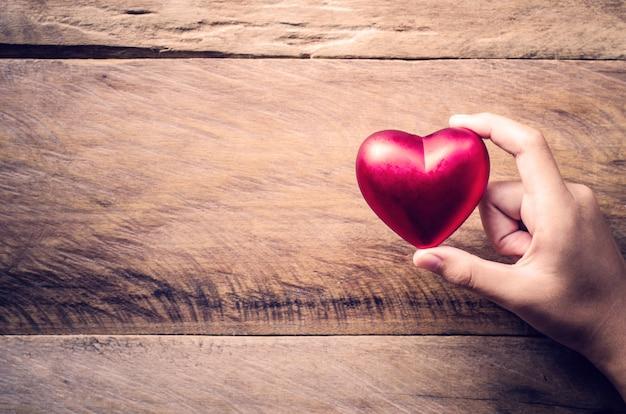 Руки женщины, давая красное сердце