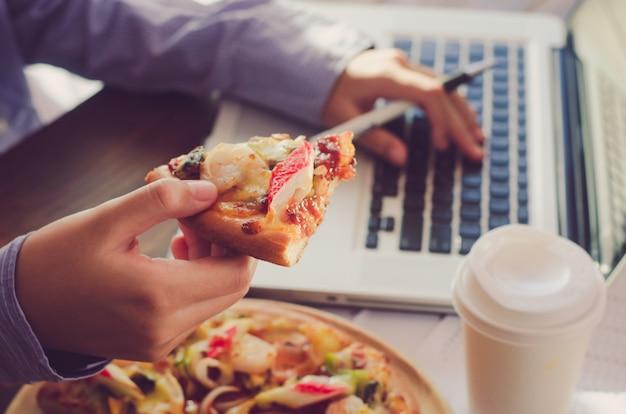 ビジネスチームは仕事中に仕事中にピザを食べています