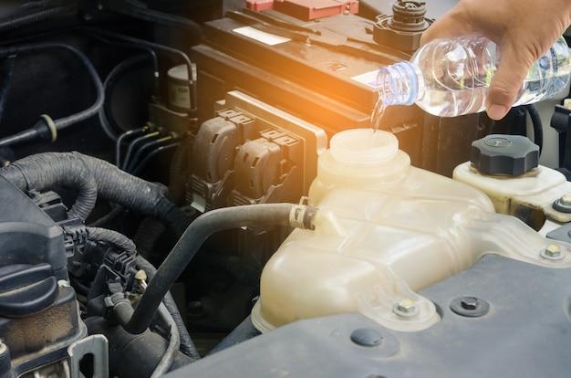 水を車のラジエーターに補充する女性。旅行前の安全のためのコンセプト