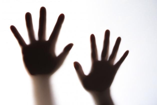 恐怖を表現する女性の手のシルエット。