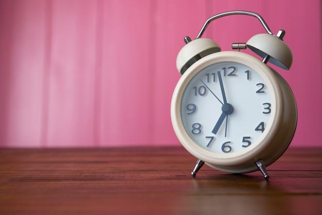 ピンク色の部屋に白い目覚まし時計が置かれています。