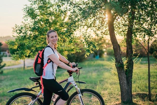 Спортивная молодая блондинка в спортивной одежде с рюкзаком едет на велосипеде и улыбается на камеру