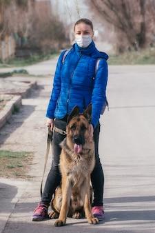 Девушка в защитной медицинской маске выгуливает собаку на улице. отдых с домашним животным во время карантина. режим самоизоляции и защиты.