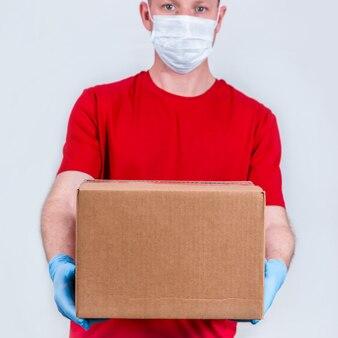 赤いユニフォームと保護医療マスクと手袋の宅配便は、段ボール箱を保持しています。隔離された注文の安全な非接触配送