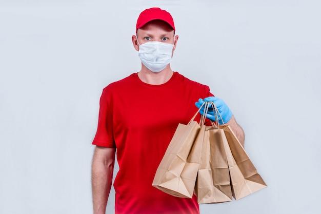 赤い制服と保護医療マスクと手袋の宅配便は紙袋を保持しています。隔離された注文の安全な非接触配送