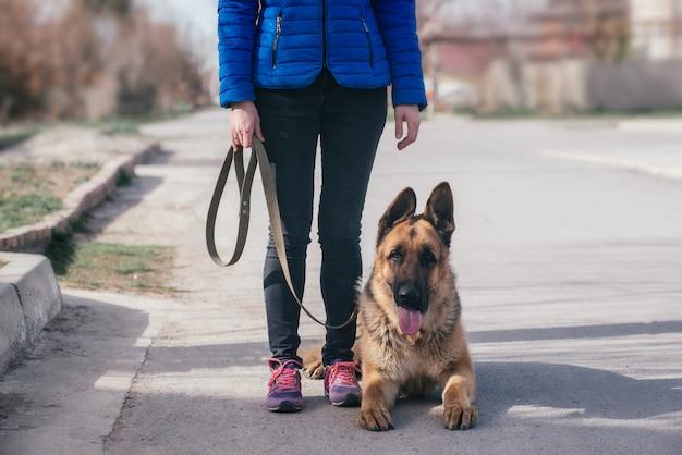 Девушка гуляет со своей собакой на улице. досуг с домашним животным. прогулка с немецкой овчаркой по городу на свежем воздухе.