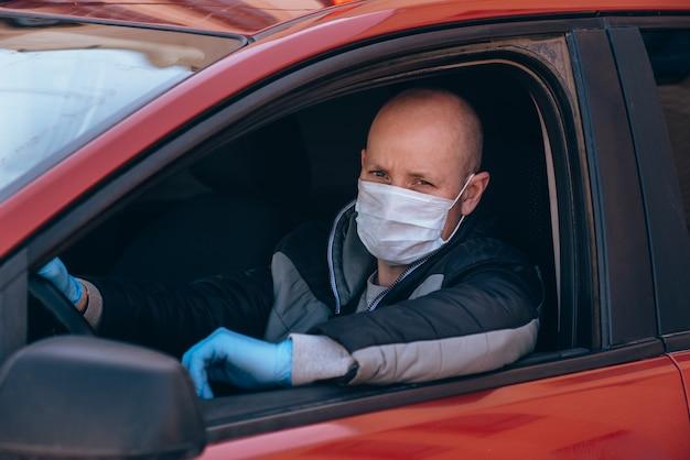 防護マスクと手袋で車を運転する男。パンデミックコロナウイルス中のタクシーでの安全運転。運転手と乗客を保護する