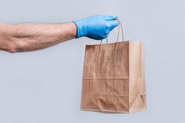 Концепция безопасной доставки в макро. рука курьера в защитных медицинских перчатках держит бумажный пакет. бесконтактная доставка заказов