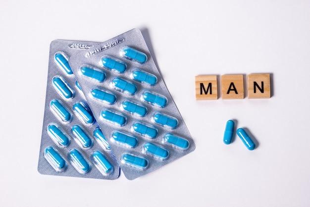 Две пачки синих капсул и надпись человек. пилюльки для здоровья людей и сексуальной энергии на белой изолированной предпосылке. понятие эрекции, потенции. лечение мужского бесплодия и импотенции.