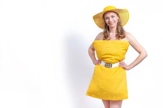 白い背景に、黄色の枕ドレスと帽子笑顔の女性。夏のコンセプトです。家の隔離を維持するための枕の挑戦。