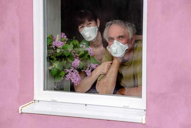 年配のカップルは抱擁します。愛情のこもった女と男がマスクで窓の外を見て、自己分離の終わりを待っています。コロナウイルスの隔離の概念は、自宅と社会的距離に滞在します。