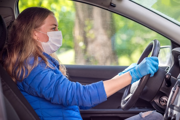 防護マスクと手袋で車を運転する女性。検疫におけるパンデミックコロナウイルス中のライフスタイルと安全運転