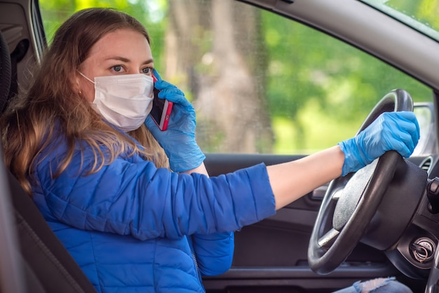 防護マスクと手袋で車を運転する女性が電話で話している。パンデミックコロナウイルス中のライフスタイルと安全なドライブ。