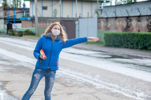 Кавказская девушка в защитной маске приветствует такси на пустой улице, стоит с зонтиком в весенний дождь и ждет машину. безопасность и социальная дистанция во время пандемии коронавируса.