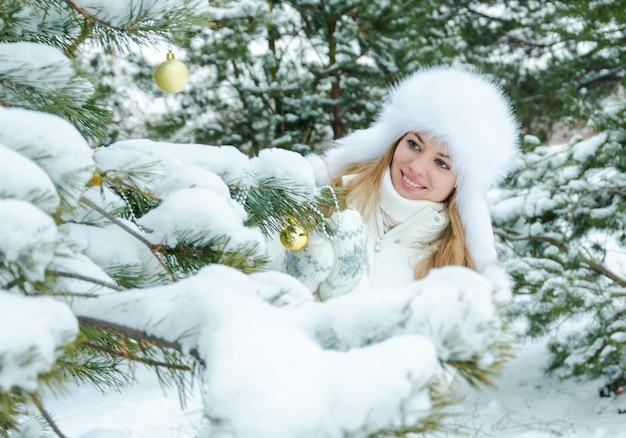 Белокурая дева в белой одежде и пушистой шапке улыбается и украшает елку в зимнем лесу