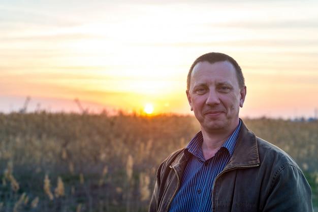 幸せな白人の成人男性農家は、仕事の日の後、彼の麦畑の前に誇らしげに立っています。日没時の豊作に男が笑います。パンの栽培、農業の概念。コピースペース。